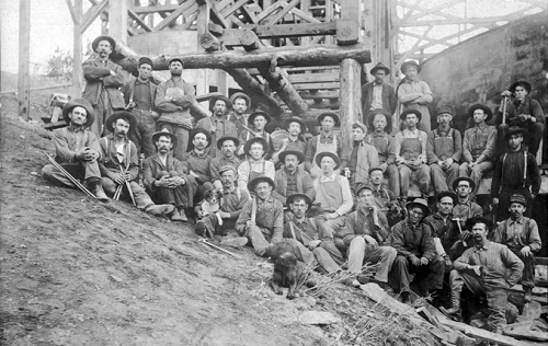 Copper miners with hammers and rock drills in front of a tramway tower at the Ferris-Haggarty mine